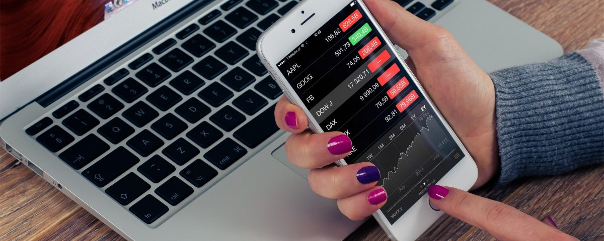 Woman holding iPhone showing stock values in red, in a financial crisis